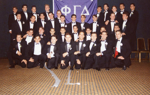 Brothers in tuxedos posing in front of chapter flag at Adelphi University chartering.